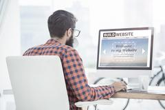 Composite image of build website interface against hipster using a computer Stock Photos