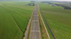 Train passing thru green meadows, high aerial perspective. Stock Footage