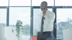 4K Portrait smiling businessman talking on phone & working at his desk Stock Footage