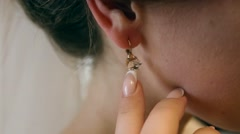 Beautiful bride wears an earring in the mirror Stock Footage