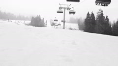 Black and white time lapse footage of ski lift transporting skiers up the hill Stock Footage