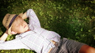 Boy lying on the ground trying to nap and squints as sun gets in his eyes Stock Footage