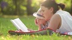 Son and mother lie on the cover in the park and read a book Stock Footage