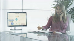 4K Portrait smiling businesswoman talking on phone & working at her desk Stock Footage