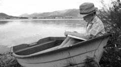 Black and white video of a boy sitting in a fishing boat and reading a book Stock Footage