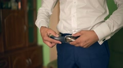 Businessman putting on a belt. Man puts on brown belt. Focus on the buckle Stock Footage