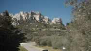 The castle of Les Baux-de-Provence village seen from afar with car traffic Stock Footage