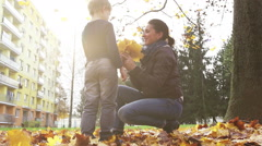Son comes to his mum, hugs her and gives her a bundle of yellow autumn leaves Stock Footage