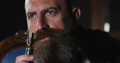 4K Extreme close up of mature businessman vaping & exhaling cloud of smoke Stock Footage