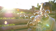 Boy Blowing Soap Bubbles At Sunset, Slow motion Stock Footage