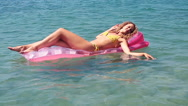 Beautiful young girl floating on a mattress in the sea Stock Footage