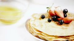 Pancakes with strawberries and bluberries are sweetened by honey Stock Footage
