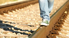 Footage turns colorful: a person walks along railway wearing sneakers Stock Footage
