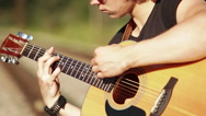 Close-up portrait of a young guitarist performing outside on acoustic guitar Stock Footage