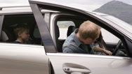 Family gets in a car with their dog and continue to ride Stock Footage