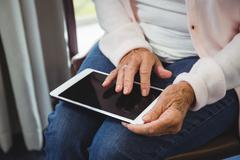 Senior woman using a digital tablet in a retirement home Stock Photos