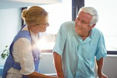 Nurse taking care of a senior man in a retirement home Stock Photos