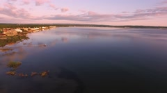 Aerial view of Traverse City shoreline at sunrise panning left Stock Footage