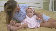 Mom gives the baby the hoop for hair to be played. Stock Footage