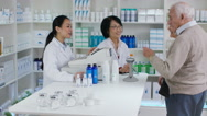 4K Friendly pharmacy worker giving prescription medication to senior couple Stock Footage
