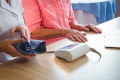 Nurse measuring the blood pressure of a senior woman in a retirement home Stock Photos