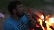 The man smokes a pipe while sitting by the fire at night Stock Footage
