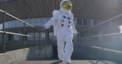 4K Funny astronaut doing a dance as he walks away from mission control building. Stock Footage