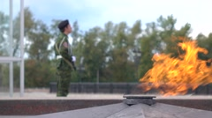 Unrecognizable guard with assault rifle and World War II eternal flame memorial Stock Footage