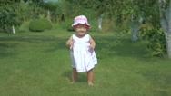 The little girl walks on a green grass. Stock Footage