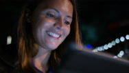Attractive female in the city at night using a digital tablet Stock Footage
