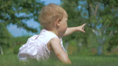 Baby crawling on the green grass in the garden. Stock Footage