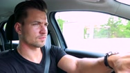 Young handsome man drives a car on the road in the town Stock Footage