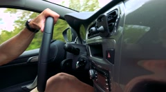 Man drives a car in the countryside - detail of steering wheel and dashboard Stock Footage