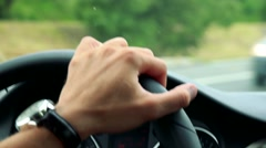Man drives a car in the city - detail of steering wheel and hand Stock Footage
