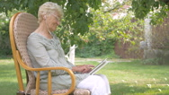 Elderly woman switches the music on the tablet. Stock Footage