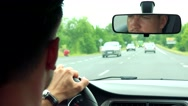 Young handsome man drives a car on the road - closeup Stock Footage