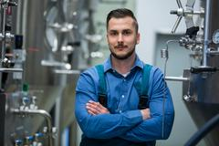 Portrait of confident maintained worker standing with arms crossed at brewery Stock Photos