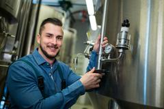 Portrait of happy brewer checking pressure at brewery Stock Photos
