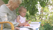 Grandma showing baby pictures in the book. Stock Footage