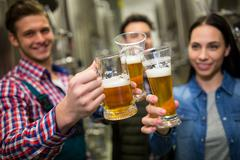 Brewers toasting beers at brewery factory Stock Photos