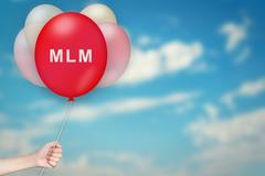 Hand Holding MLM or Multi level marketing Balloon Stock Photos