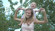 Baby sitting on mother's neck. Stock Footage