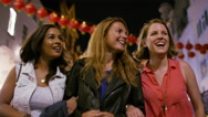 Three female friends walking through a festival district at night in the city Stock Footage