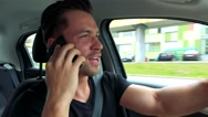 Young handsome man drives a car and phones with smartphone - buildings  Stock Footage