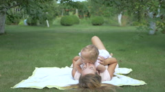 Baby with her mom lying on the rug in the garden. Stock Footage