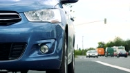 Car stands beside the road with passing cars Stock Footage