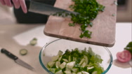 Female moves chopped greens from board into salad Stock Footage