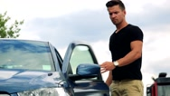 Young handsome man gets out of the car and walk away - countryside Stock Footage
