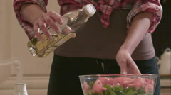 Woman adds oil into the salad Stock Footage