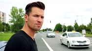 Young handsome man stands next to the car and looks around -  road with cars Stock Footage